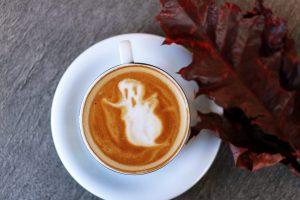 Halloween-spøkelse i skummet på ein kaffikopp. Foto.